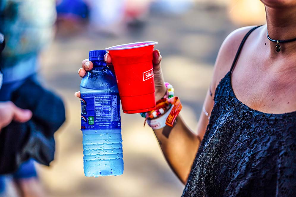 Leadership in alcohol: A lady holding water bottle and Smirnoff drink